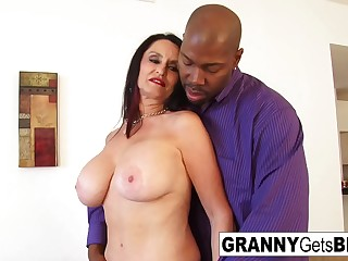 Busty dark-haired granny takes the black cock in her raw pussy